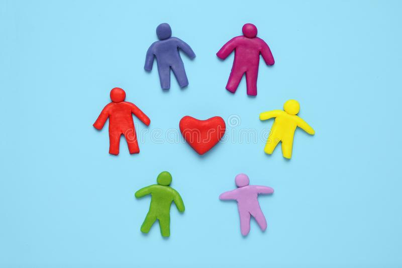 Figure multicolori del plasticine della gente e del cuore Razzismo ed uguaglianza della gente in mondo fotografia stock libera da diritti