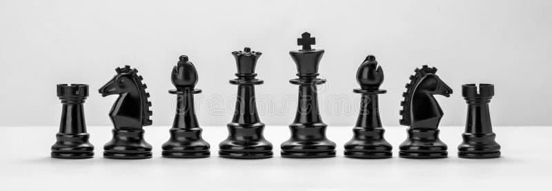 Figure nere di scacchi isolate sui precedenti bianchi fotografie stock libere da diritti