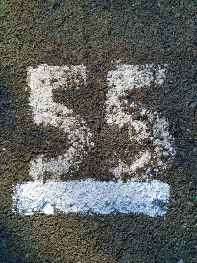 The figure `55` painted with white paint on the gray asphalt. royalty free stock photography