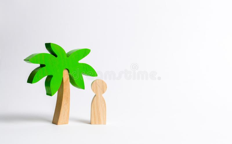 The figure of the person costs under a wooden palm tree on a white background. Vacation or trip. Stuck on a desert island. royalty free stock photography