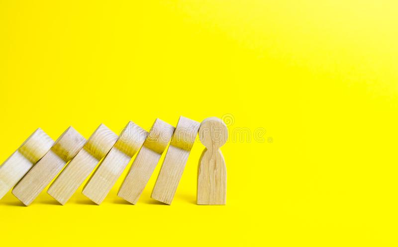 The figure of a person stops the fall of a set of figures like dominoes. Colaps dominoes. Strong leader and reliable support. And loyal. business training, self stock images