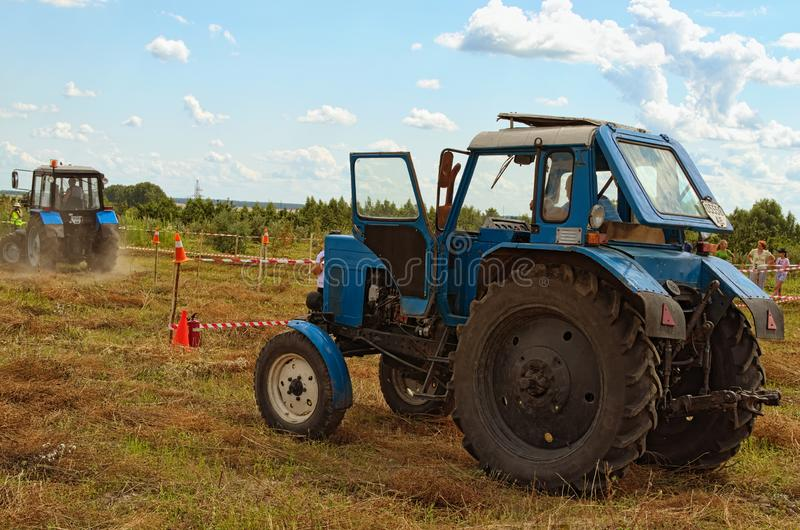 Figure piloting competition at the field. Blue old tractor is waiting for it attempt. Next participant is ready to start stock image