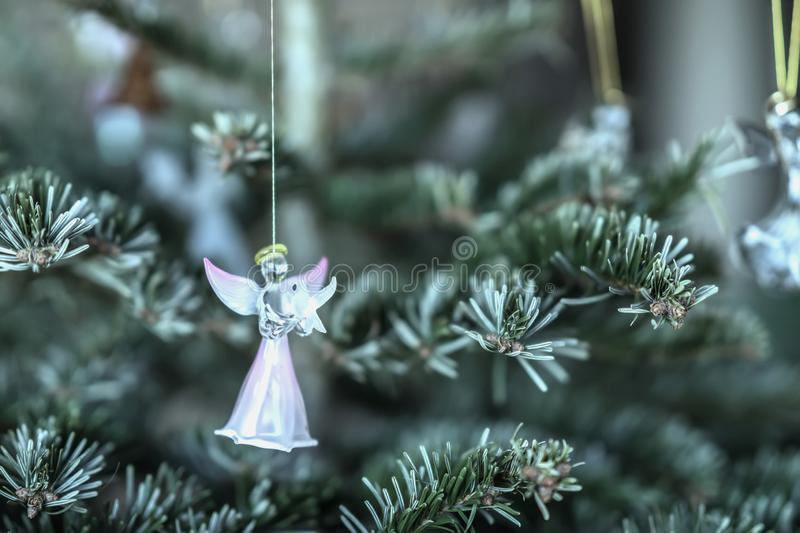 Figure of pink angel with dove in his hands on a branch of spruce, glass Christmas decoration, background with copy stock images