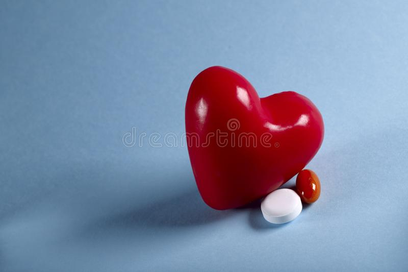 The figure of a red heart and two pills on a blue background. Horizontal, close-up, free space, no people, side view. Medicine concept. Crisis of opioid royalty free stock photos