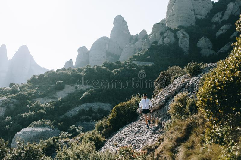 Athletic strong man runs trail ultra marathon stock photo