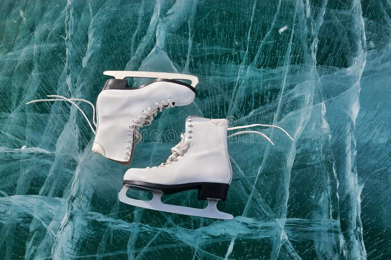 Figure skates at transparent cracked ice surface close up. Winter sport concept. Lake Baikal. Ice stock image