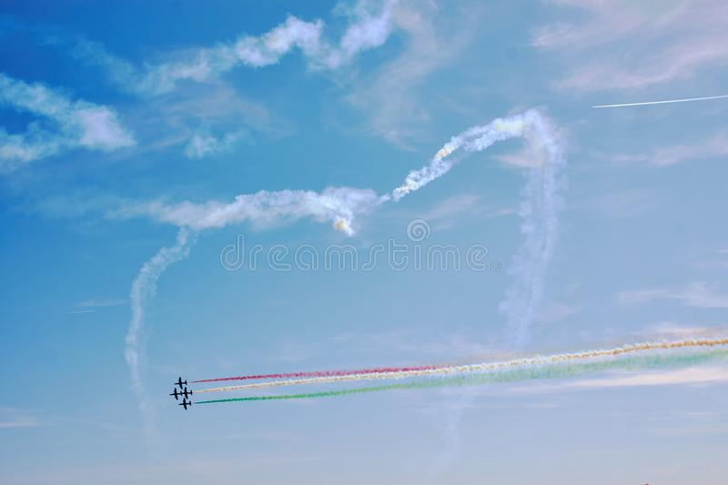 Air show. A figure in the sky in the shape of a heart from a smoke and ahead of an air fighter against a blue sky. Bright air show royalty free stock photography