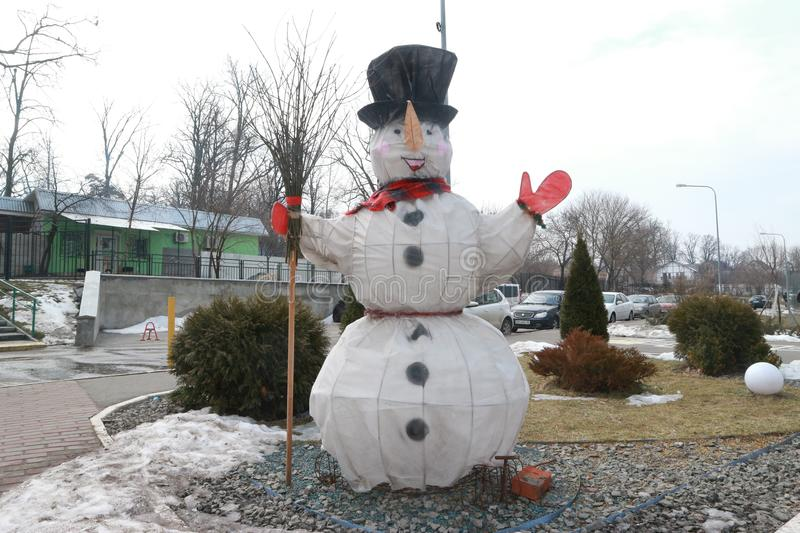 A figure of a snowman with a broom in the yard stock photos