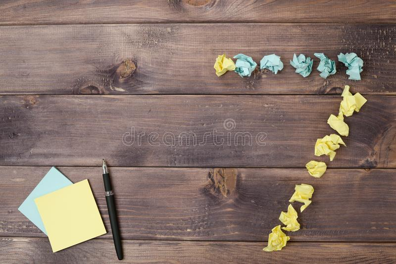 Figure 7 on a table. Crumpled pieces of paper in the form of balls, forms figure 7 on a dark wooden table. top view stock image