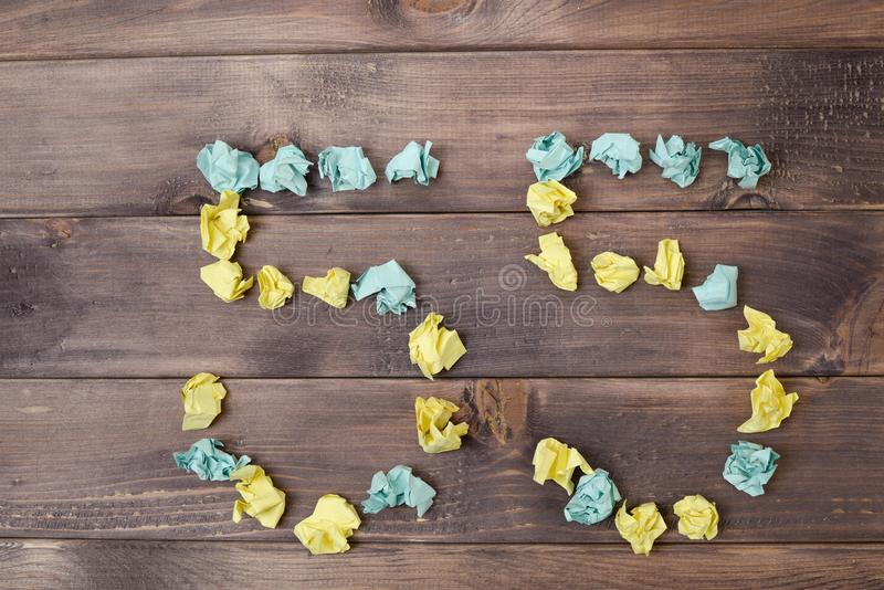 Figure 55 on a table. Crumpled pieces of paper in the form of balls, forms figure 55 on a dark wooden table. top view royalty free stock photos