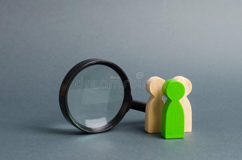 Figure trois humaine en bois se tient près d'une loupe sur un fond gris Le concept de la recherche des personnes et des travaille photos stock