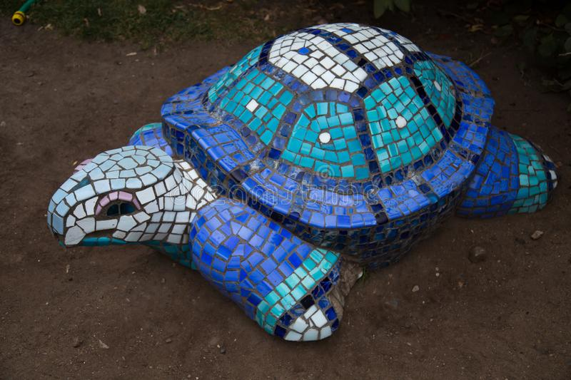 The figure of a turtle, made of a mosaic of blue and white. The design of the city Park. Art stock photos