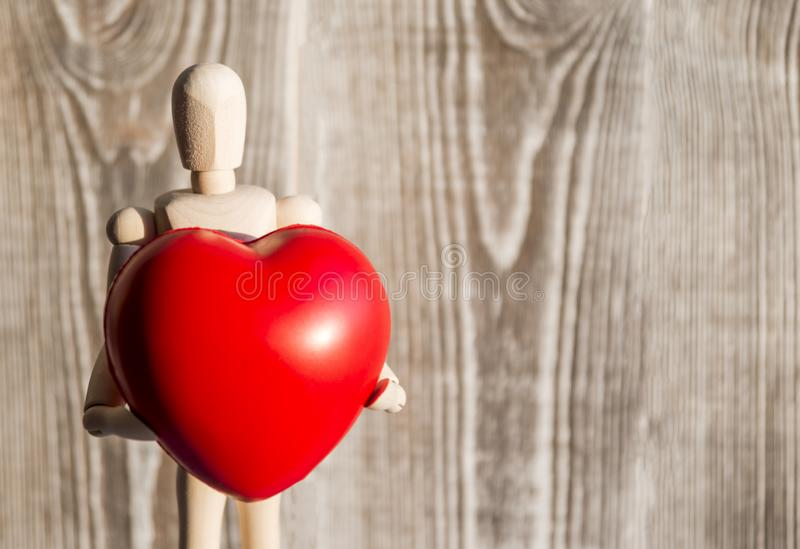 The figure of a wooden man holds a red heart in his hands stock photography