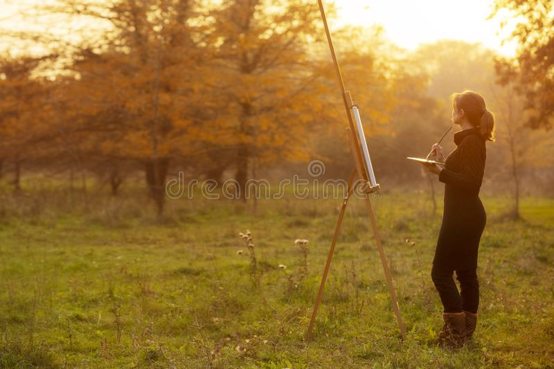 Figure of young woman artist painting a picture on the easel, girl enjoying autumn nature and working inspired by beautiful. Landscape with a brush and a stock photos