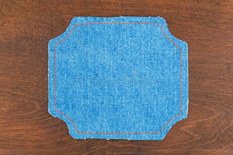 Figured frame made of denim lying on dark wooden surface royalty free stock images