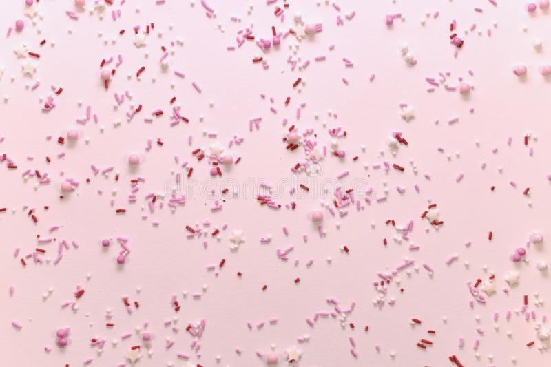 Figured sugar topping in pink tones. Figured sugar topping in pink tones, scattered on a light surface. View from above royalty free stock images