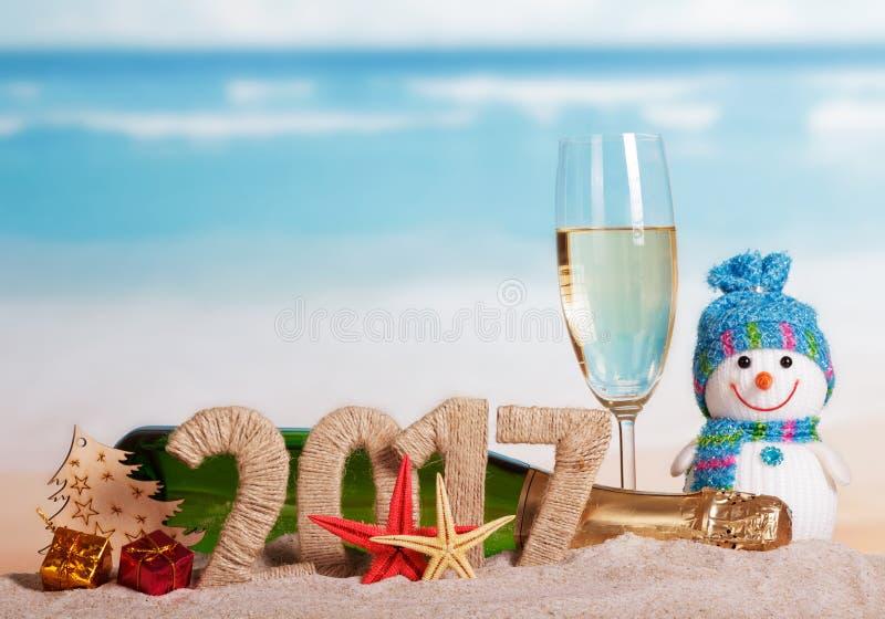 Figuren 2017 champagnefles, glas, sneeuwman, Kerstboom tegen overzees stock afbeeldingen