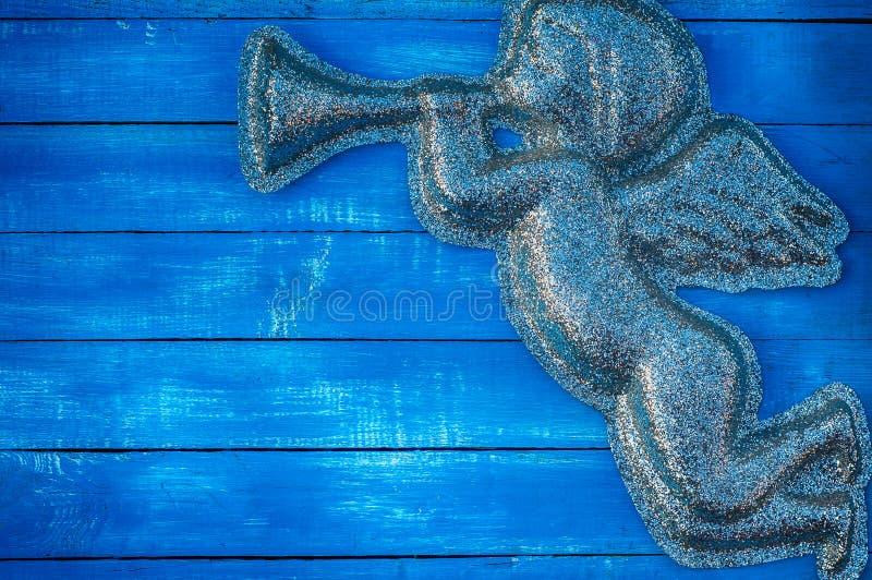 Figurera ängeln av skinande partiklar på en blå träbakgrund arkivbild