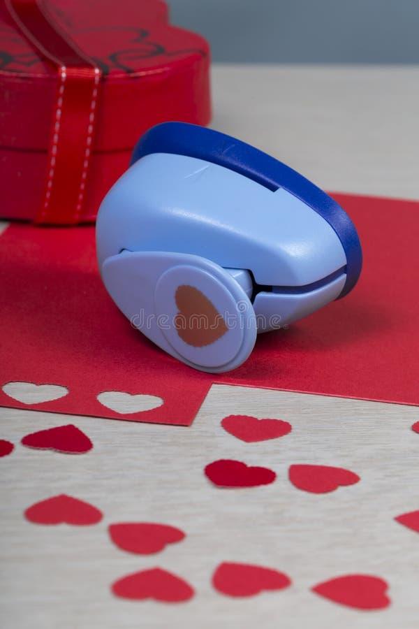 Figurerad plast-pappersstansmaskin och handgjorda röda hjärtor arkivfoto