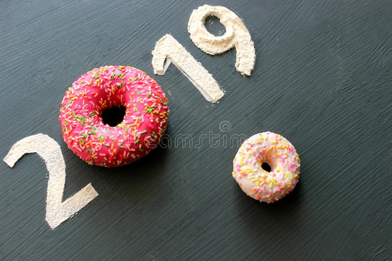 Figures 2019 on a black background filled with flour, pink donut instead of the number 0, the concept of the new year, sweet life stock photos