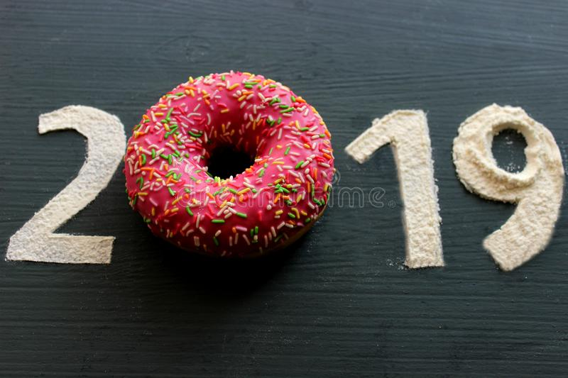 Figures 2019 on a black background filled with flour, pink donut instead of the number 0, the concept of the new year, sweet life royalty free stock photos