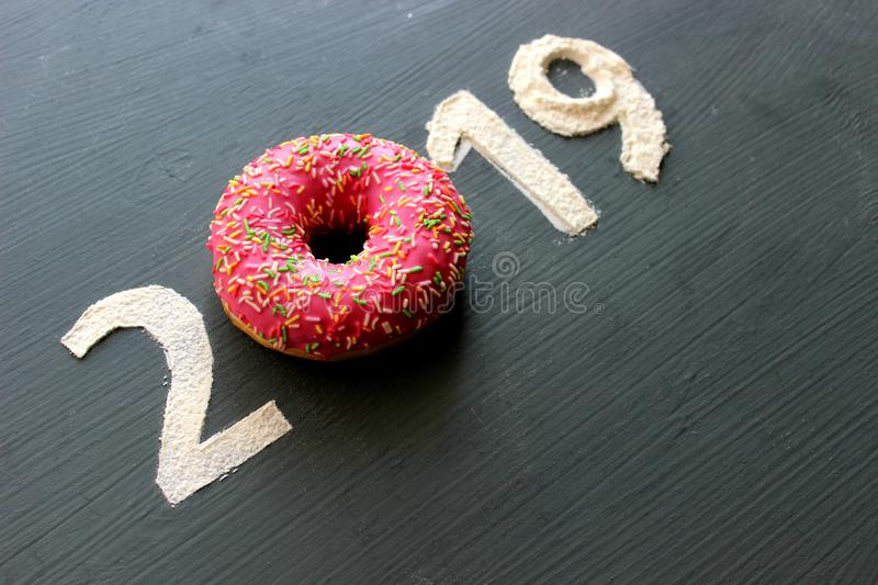 Figures 2019 on a black background filled with flour, pink donut instead of the number 0, the concept of the new year, sweet life royalty free stock image