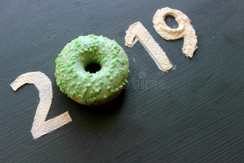 Figures 2019 on a black background filled with flour, pink donut instead of the number 0, the concept of the new year, sweet life royalty free stock photography