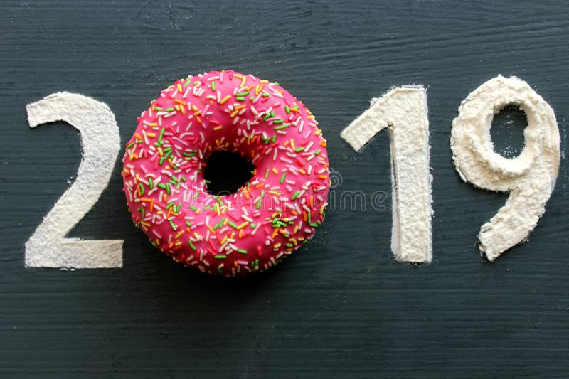 Figures 2019 on a black background filled with flour, pink donut instead of the number 0 stock photo