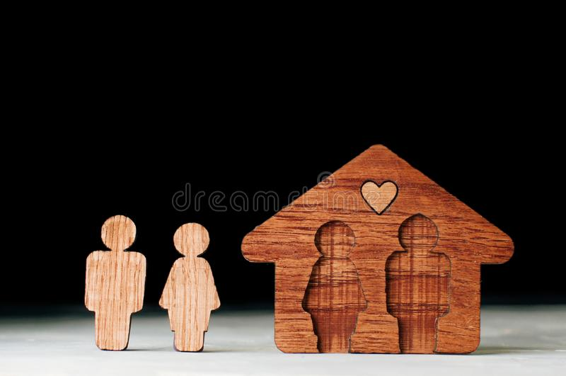Figures of couple and house on black background with copy space. Family home concept. Wooden figures of man and woman near house on black background with blank royalty free stock image