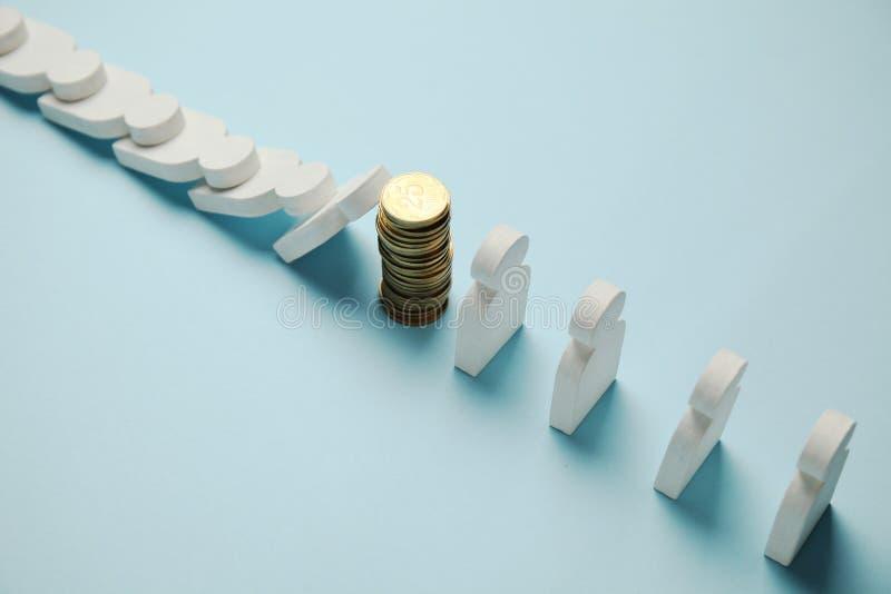 Figures des personnes dans la rang?e avec des pi?ces de monnaie, effet de domino Stabilit? financi?re et ?conomique photographie stock