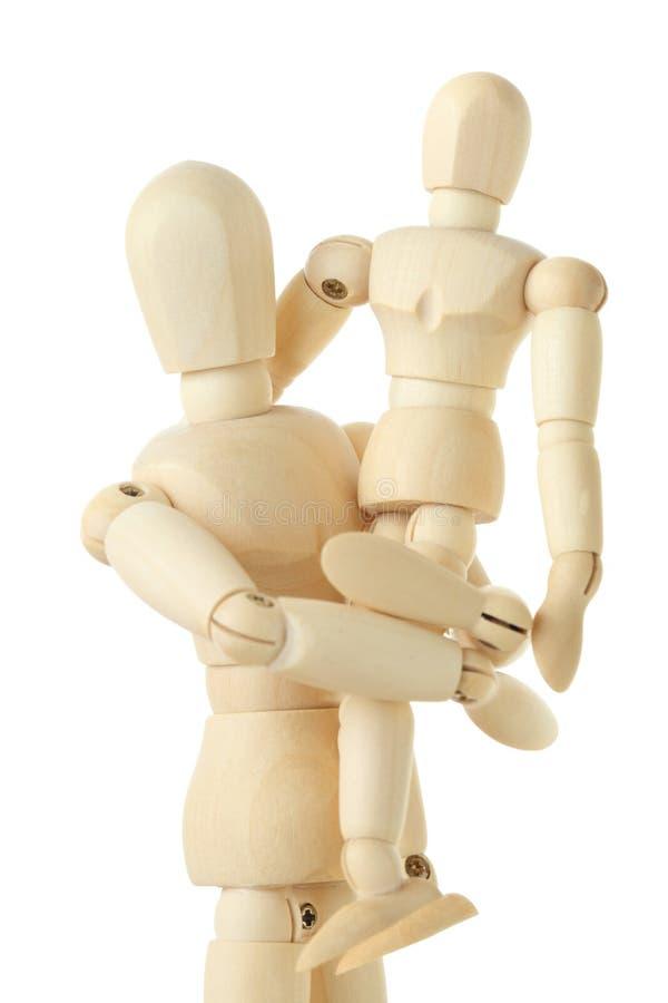 Figures en bois d'enfant se reposant sur des mains de parent photos stock