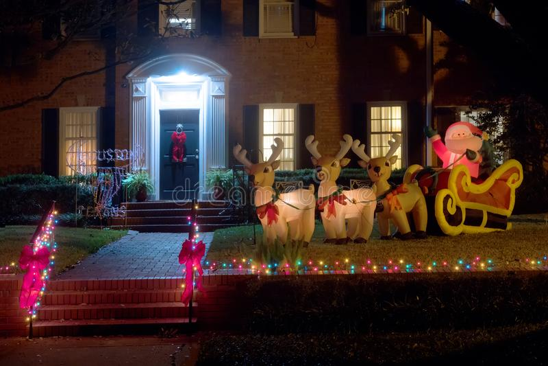 Figures gonflables : Santa Claus dans un traîneau avec des cerfs communs près du h image libre de droits