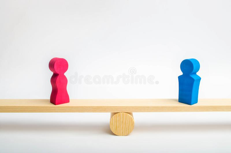 Figures of a man and a woman on the scales. inequality concept : man and women on a weighing balance, gender pay gap. divorce. Div. Ision of property in court royalty free stock photo