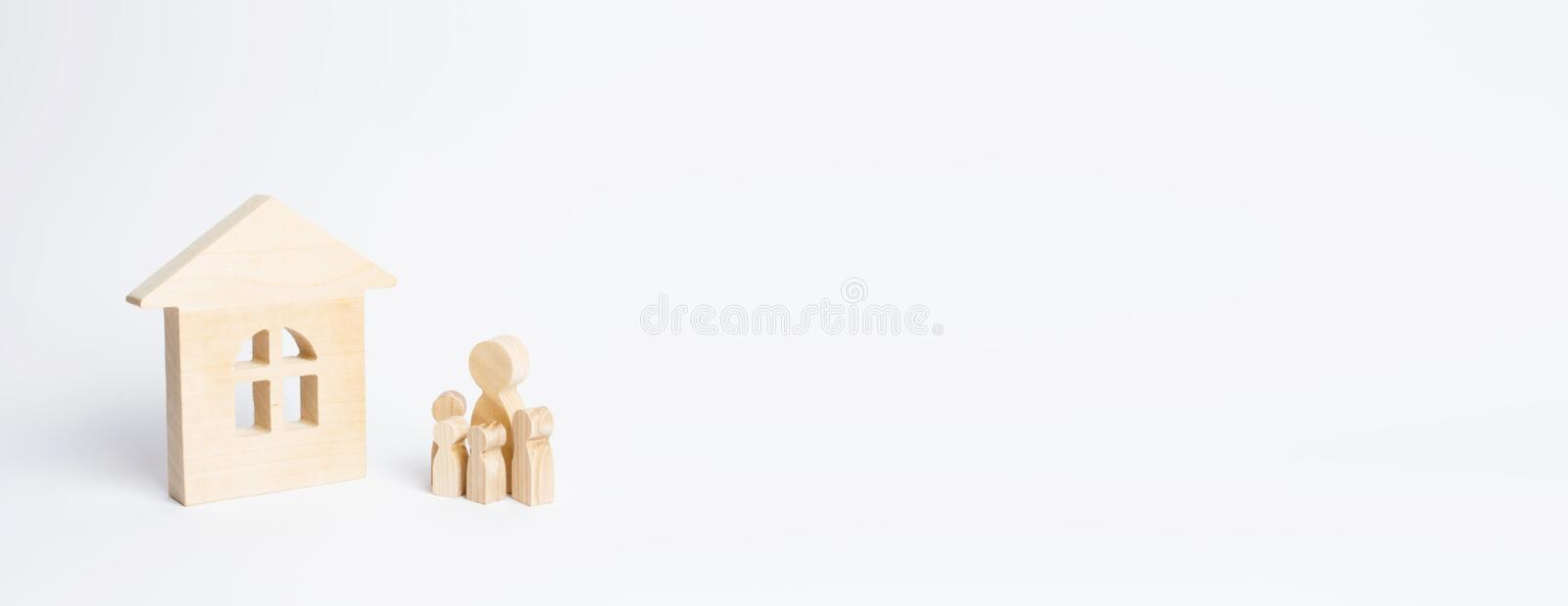 Figures of people with children stand near a wooden house on a white background. The concept of real estate and affordable housing stock photo
