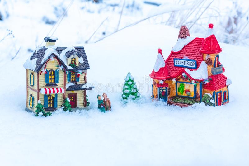 The figures of people standing in the snow between the two houses and a small New Year tree. royalty free stock image