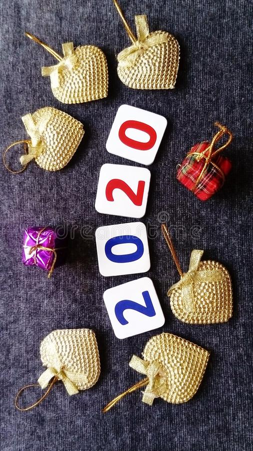 Figures 2020 in red and blue, surrounded by golden hearts and small gifts. Happy New Year Greeting Card stock photos