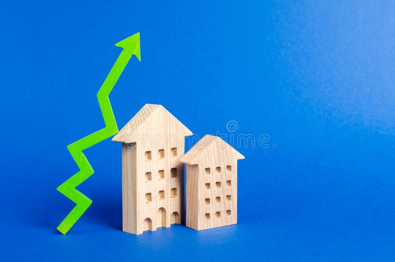 Figures of residential buildings and green arrow up. Increasing cost and liquidity of real estate. Attractive investing. Rising prices or renting. growth of stock photography