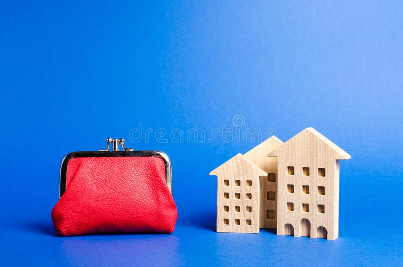 Figures of residential buildings near a large red wallet. concept of the cost of maintaining the building and utility bills. Modernization of housing stock images