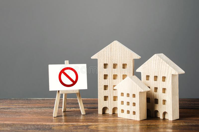 Figures of residential buildings and red prohibition sign no. Inaccessible and expensive housing. Seizure and freezing of assets. By a bank, court. Restrictions royalty free stock photos