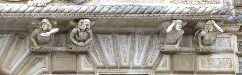 Figures sculptées lunatiques sur des contrefiches d'un balcon images stock
