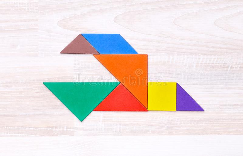 Figures into shape of bird. Flay lay of colorful tangram figures arranged in shape of bird on wooden table stock photography