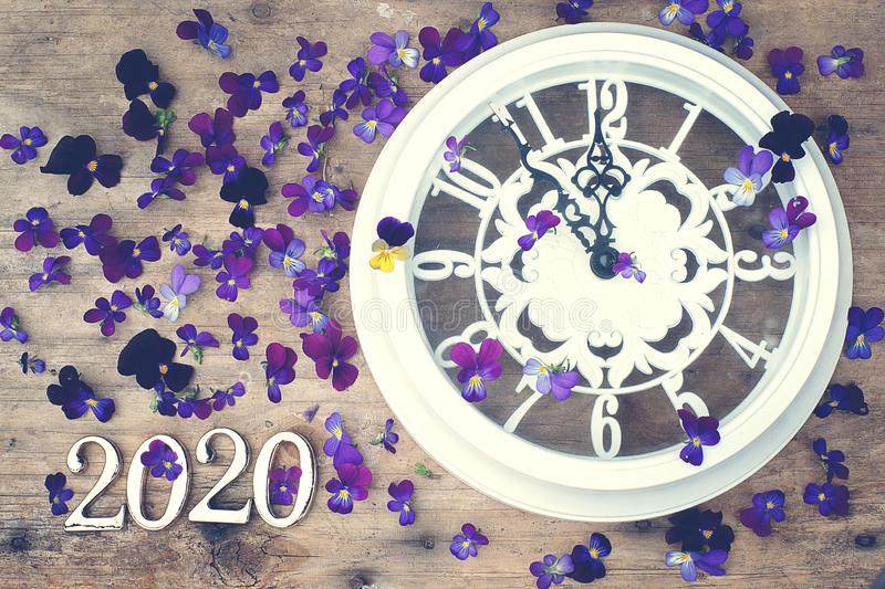Figures 2020 on a wooden background next to purple pansy flowers and a white clock showing five minutes to midnight.  royalty free stock photo