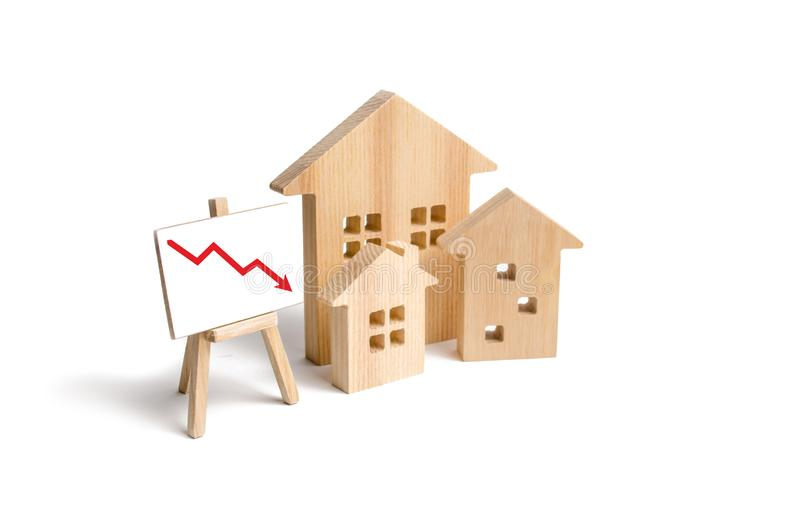 Figures Wooden houses and red arrow down. The concept of falling prices and demand for real estate, crisis and recession. The fall in the rate of construction royalty free stock photography