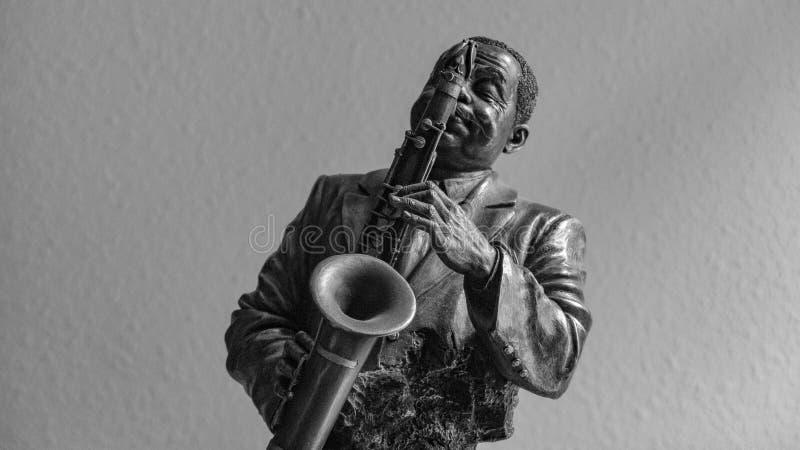 Figurilla de bronce de un hombre que está tocando el saxofón fotografía de archivo libre de regalías