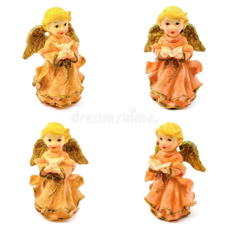 Figurilla de los ángeles de la porcelana con el libro y la paloma aislados en el fondo blanco fotografía de archivo