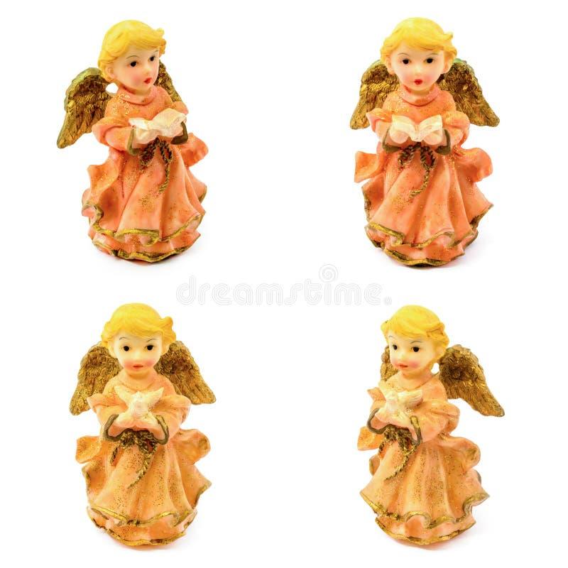 Figurilla de los ángeles de la porcelana con el libro y la paloma aislados en el fondo blanco fotos de archivo