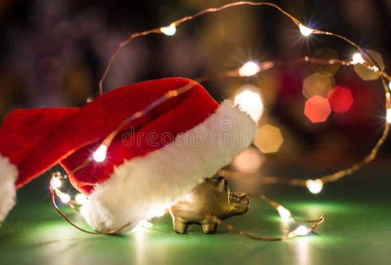 Figurilla de oro de un cerdo con un sombrero de Papá Noel, el concepto del Año Nuevo imagen de archivo