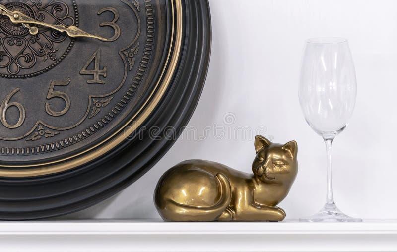 Figurilla de un gato contra la perspectiva de un reloj marrón y de una copa de vino foto de archivo
