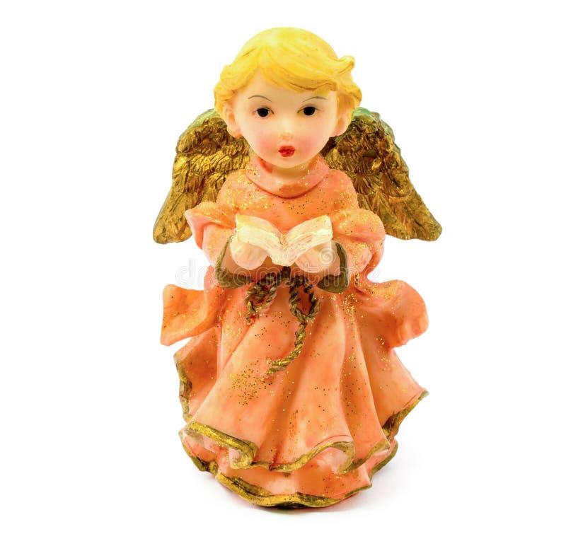 Figurilla del ángel de la porcelana con el libro aislado en el fondo blanco fotografía de archivo