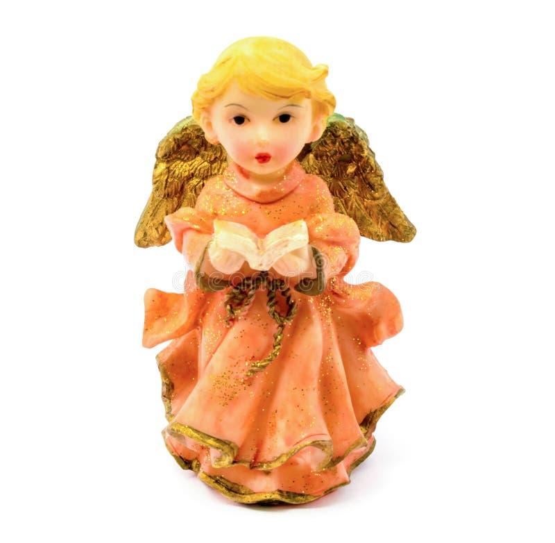Figurilla del ángel de la porcelana con el libro aislado en el fondo blanco fotografía de archivo libre de regalías